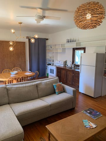 The cabin features a full kitchen, comfy sofa with a queen size pullout, separate bedroom, full bathroom, large dining table, and private back deck.