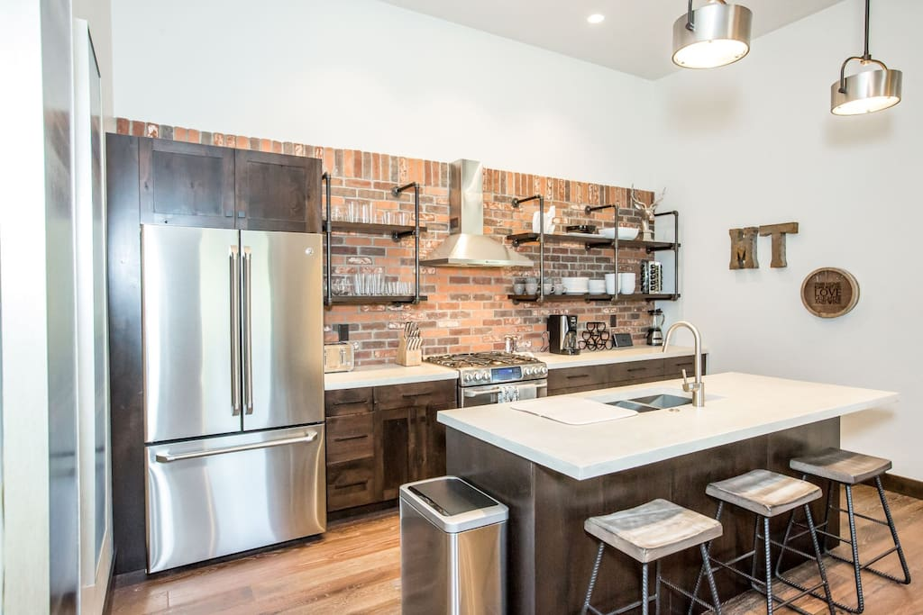 Kitchen features stainless steel appliances with brick backsplash.