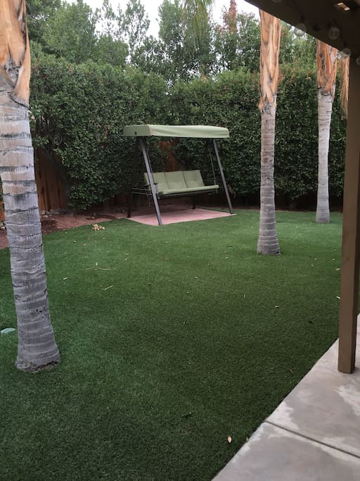 Private backyard w artificial turf, swing, covered patio w lights, table and chair