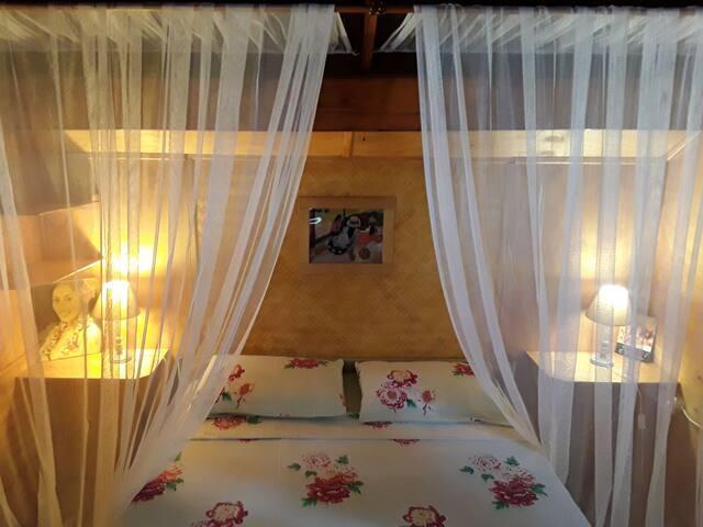 La chambre avec 1 lit de 150, ventilateur, ouvertures fenetres bois avec moustiquaires donnant sur la mer