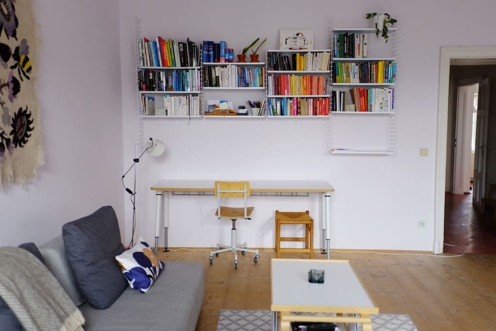 Living room with a desk and small library
