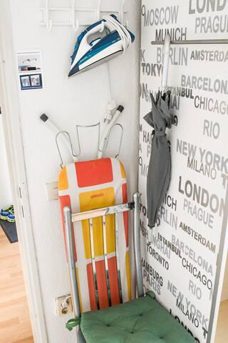 Modernes Bügeleisen mit Bügelbrett und ein Regenschirm bei Bedarf