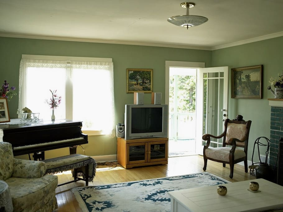 Sunny living room with piano, fireplace and satellite tv