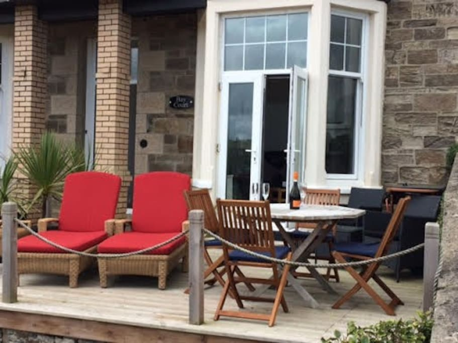 A patio table and four cushioned chairs for eating al fresco