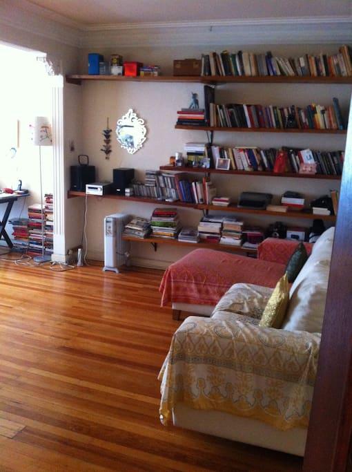 Libros, radio, sofá y loft seat que se convierte en cama.