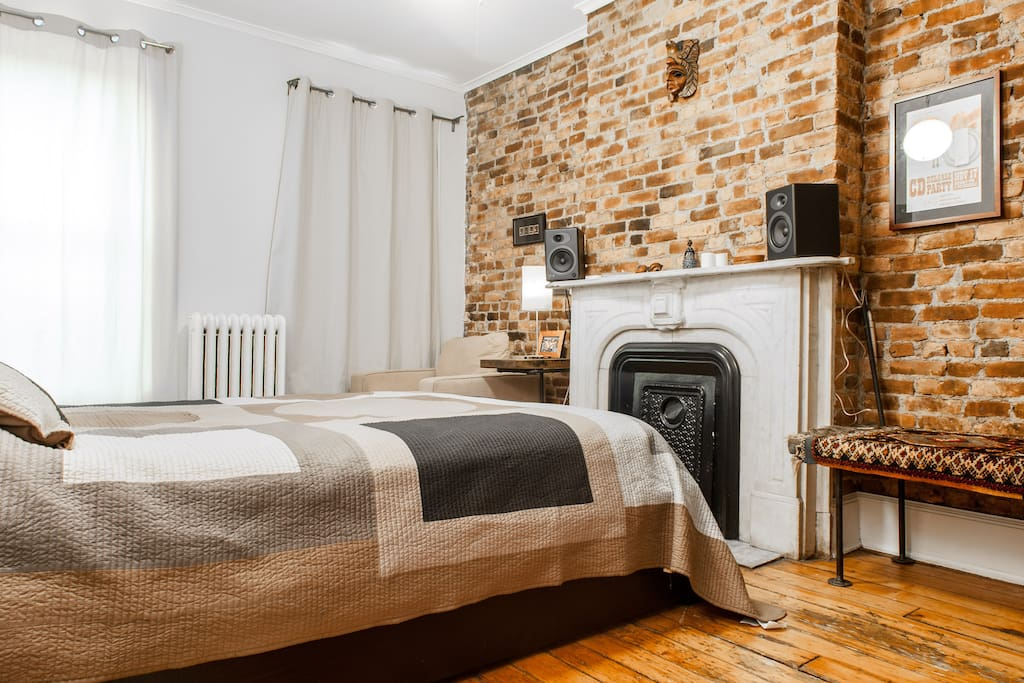 quiet, large bedroom with great daylight, exposed brick and  a cosy reading nook and a view of the back yard