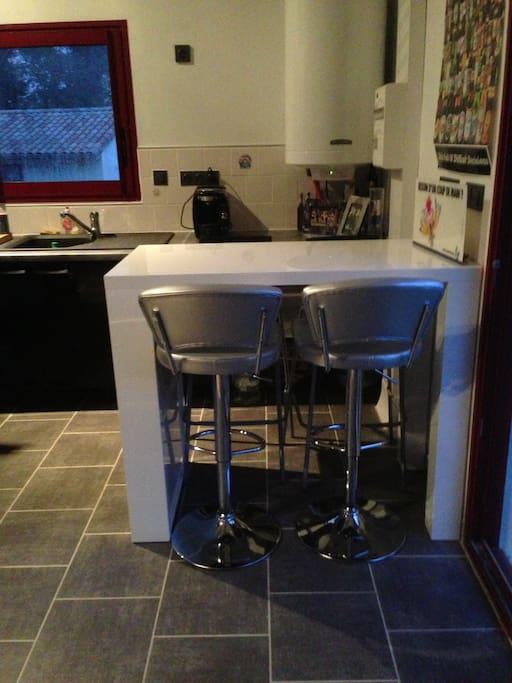 Coin repas, avec table haute et 4 chaises.