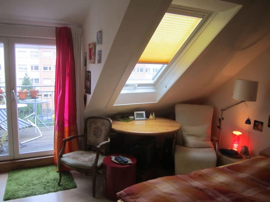 Zimmer mit Dachschrägenfenster und Balkonzugang