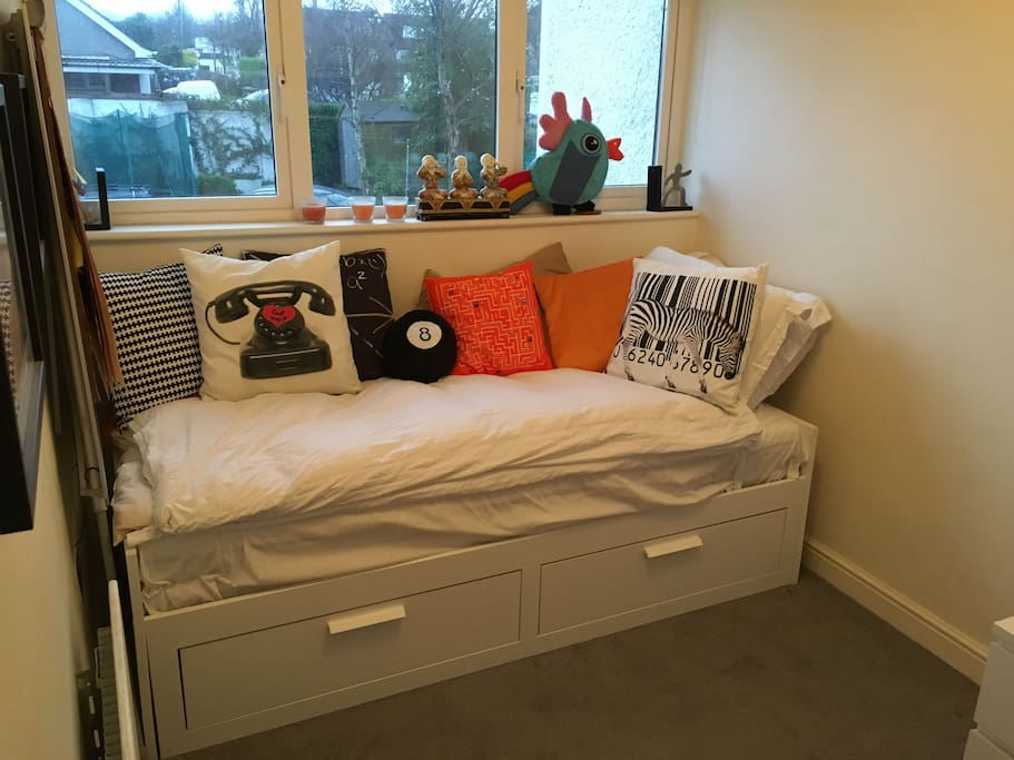 Bedroom with bed folded in as wooden day bed