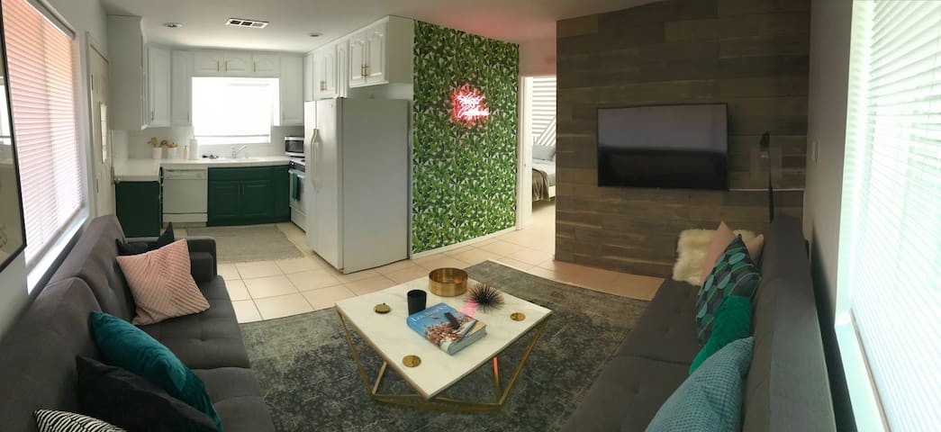 The living room is adjacent to the kitchen and has two sofas that fold flat to become full sized beds. A curved SmartTV mounted on the wood wall is beautiful.