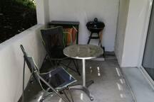 Petite terrasse et barbecue avec baie vitrée donnant sur le studio