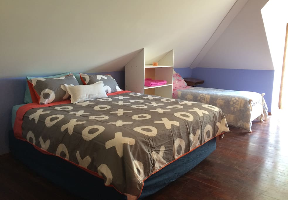 King size bed and single bed along one wall. There is also a fold-out sofa bed.