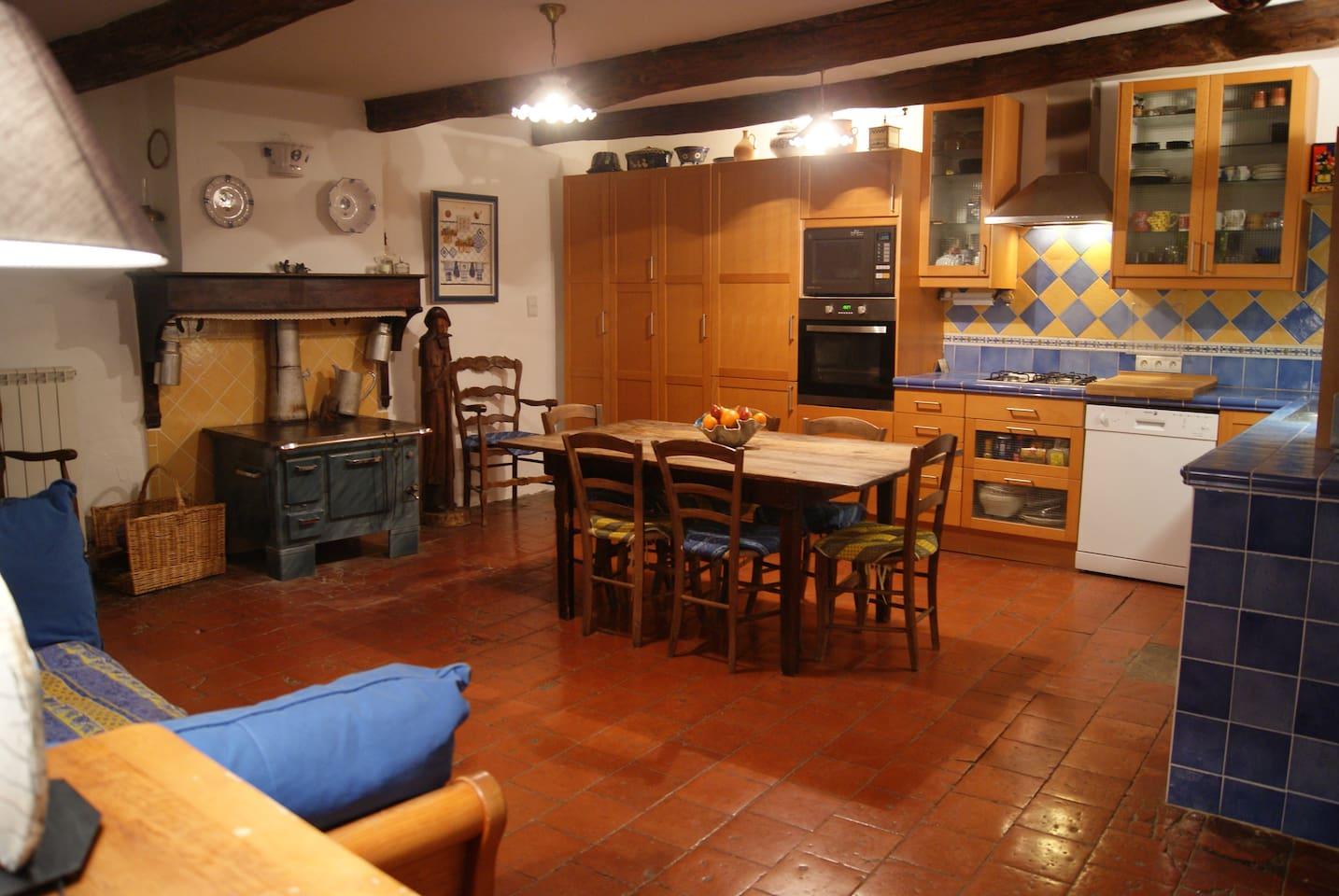 Une grande cuisine accueillante qui donne sur un grand salon/salle à manger