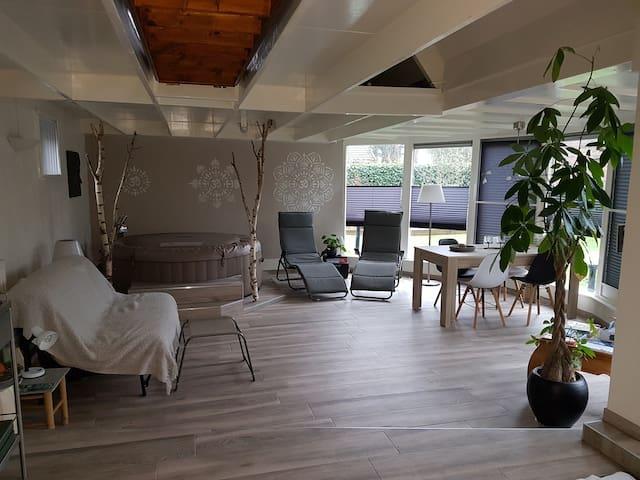Overzicht leefruimte, Slaapbank, hottub, relaxstoelen, tafel met stoelen