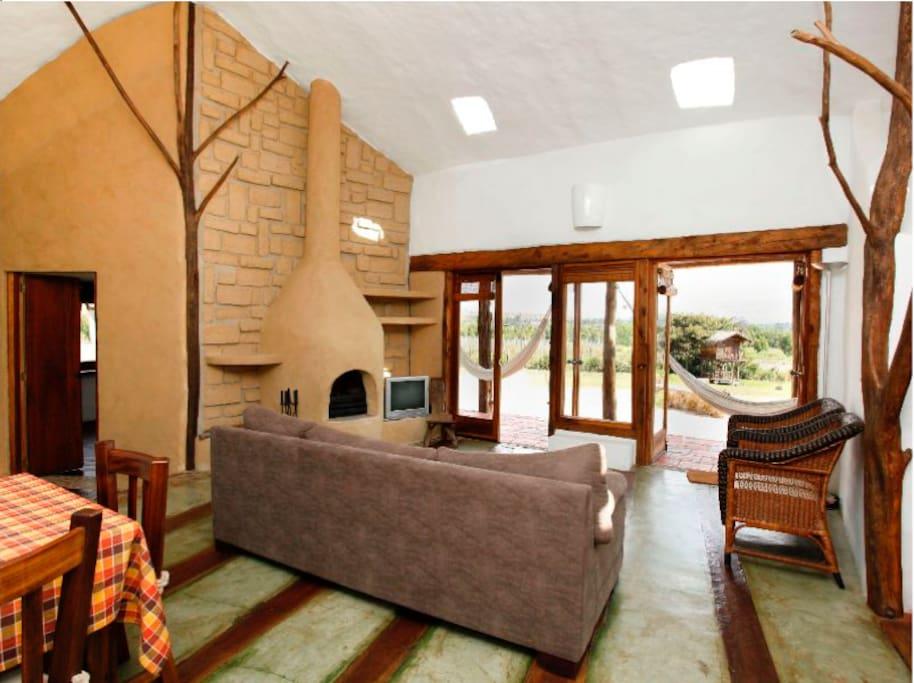 Sala con vista al paisaje. Al fondo casita  de madera para los niños.