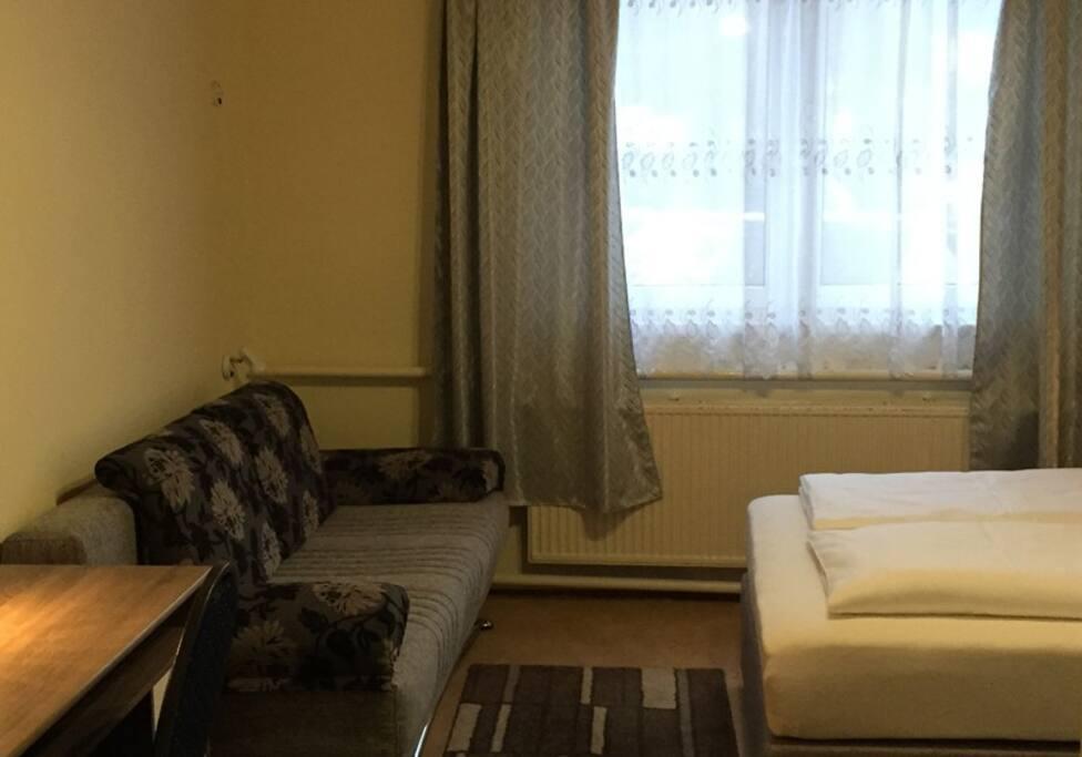 Уютная комната с двухспальной кроватью и диваном