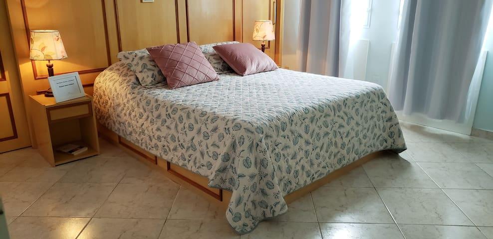 Quarto amplo com abajur, ar condicionado split, cama queen, cômoda, closet, criado mudo, frigobar,  janelas com cortina (voil e blackout) e ventilador.