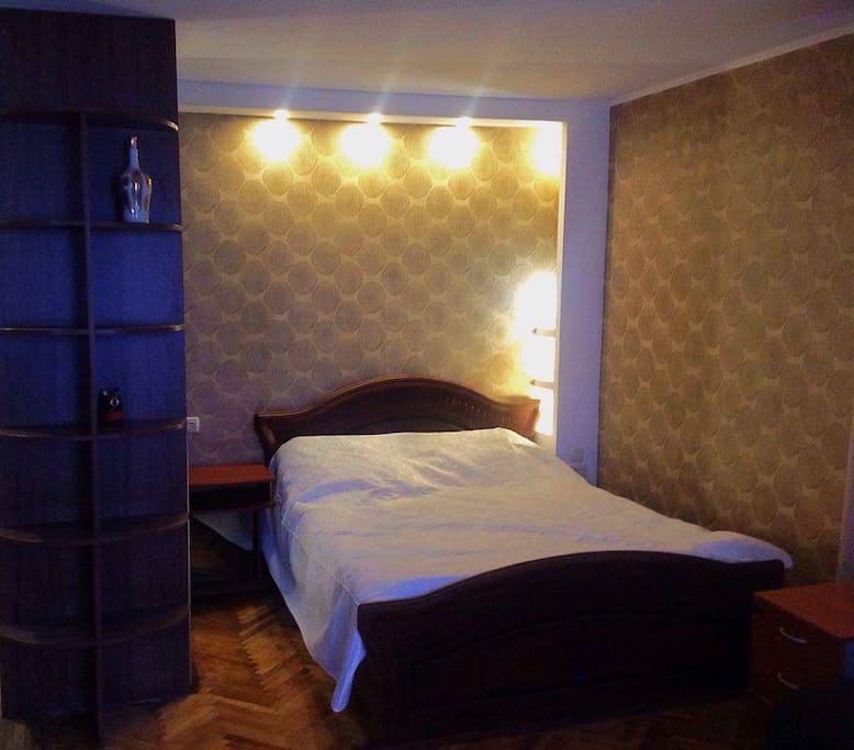 Широкая красивая кровать и белоснежное постельное белье.