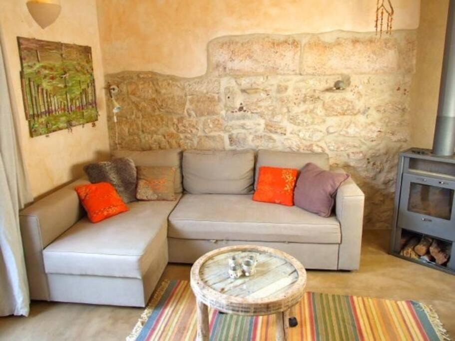 Wohnzimmer mit gemütlicher Sitzecke (Schlafsofa) und Kaminofen für den Winter