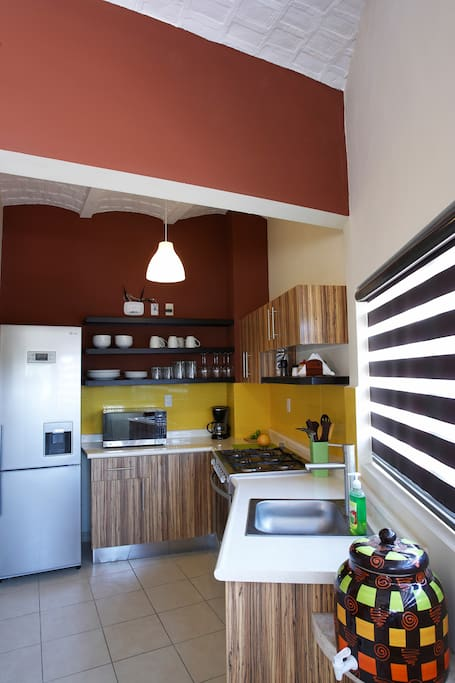 Kitchen with zebra wood cabinets, Italian contemporary tiles,  full size fridge, pots, pans, plates, glassware, cutlery