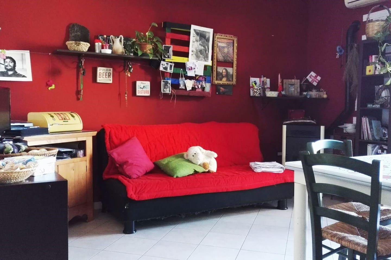 Cucina-soggiorno con divano letto e balconcino.