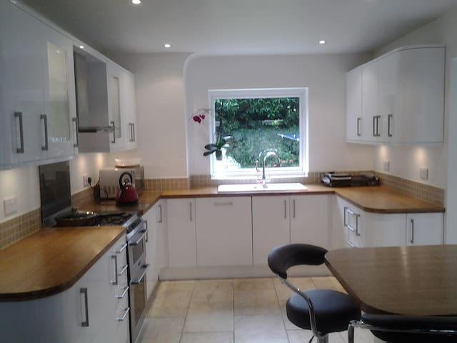 Spacious kitchen with breakfast bar, corner sofa & tv