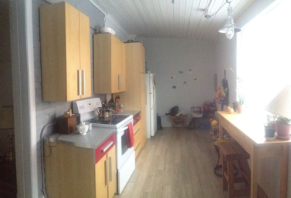 Super bright kitchen! Lots of counter space- perfect for cooking or working. Exposed brick walls.