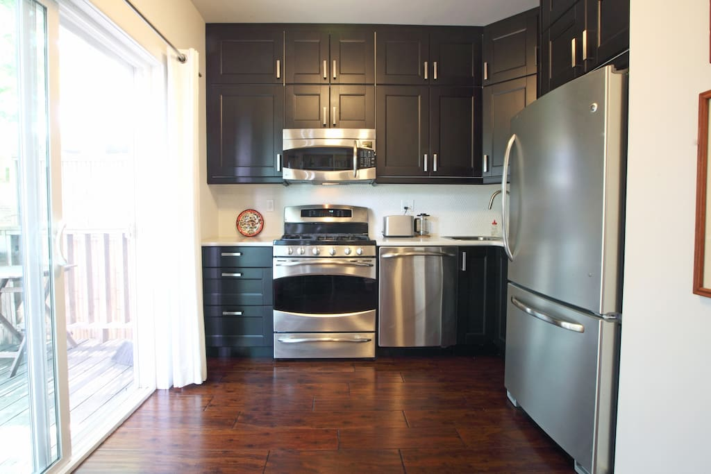 Kitchen with gas stove, dishwasher, toaster, tea kettle, coffee maker, large fridge