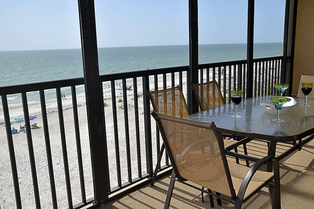 Beautiful beachfront views with a glider, large dining table, and chaise lounge