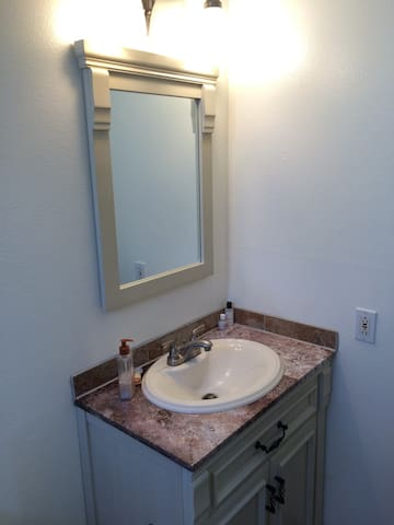 New vanity in private bath.  Shower/tub combo on other wall.
