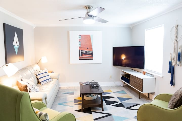 """Bright living room with ample seating around the 50"""" LG smart HDTV."""
