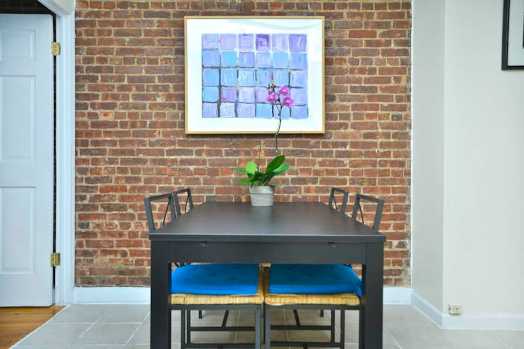 Dining table and one of the exposed brick walls in the apartment.