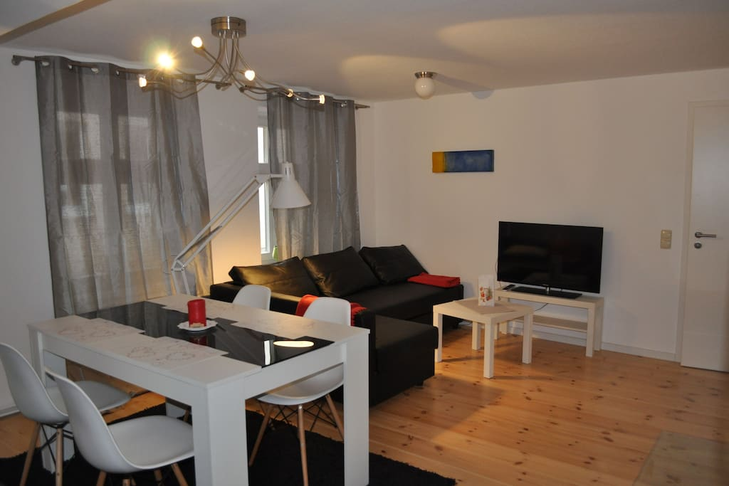 Wohnzimmer mit Essplatz und Schlafcouch, TV.