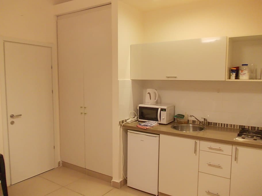 Nice kitchen area and closet, high ceilings. Kitchen has stove, oven, kettle, microwave, pots, pans, glasses, dishes and silverware.