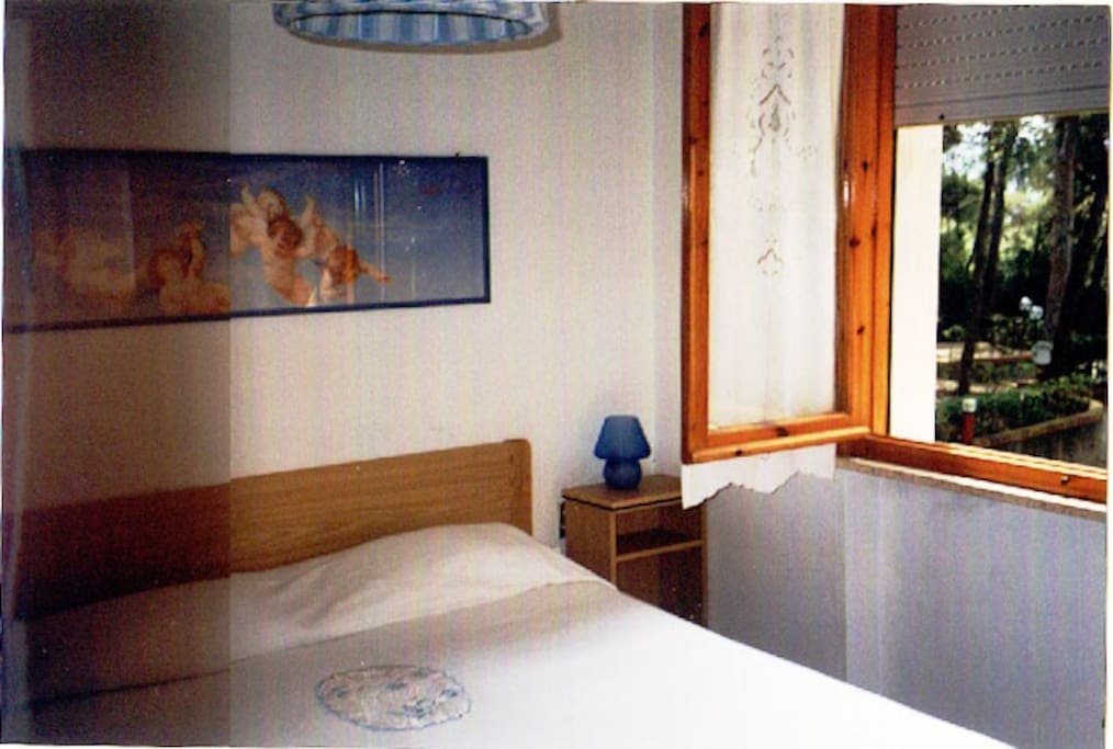 The bedroom with double bed and the view of the swimmingpool