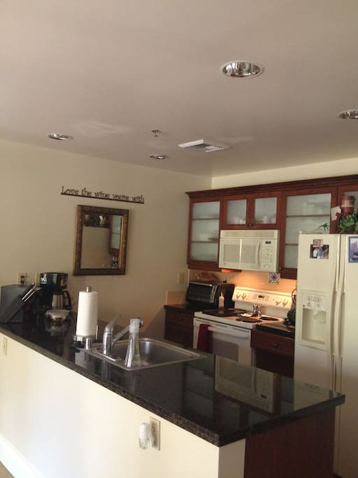 A full kitchen, stocked with all dishware, pots/pans, coffee maker, blender, paper products, etc.