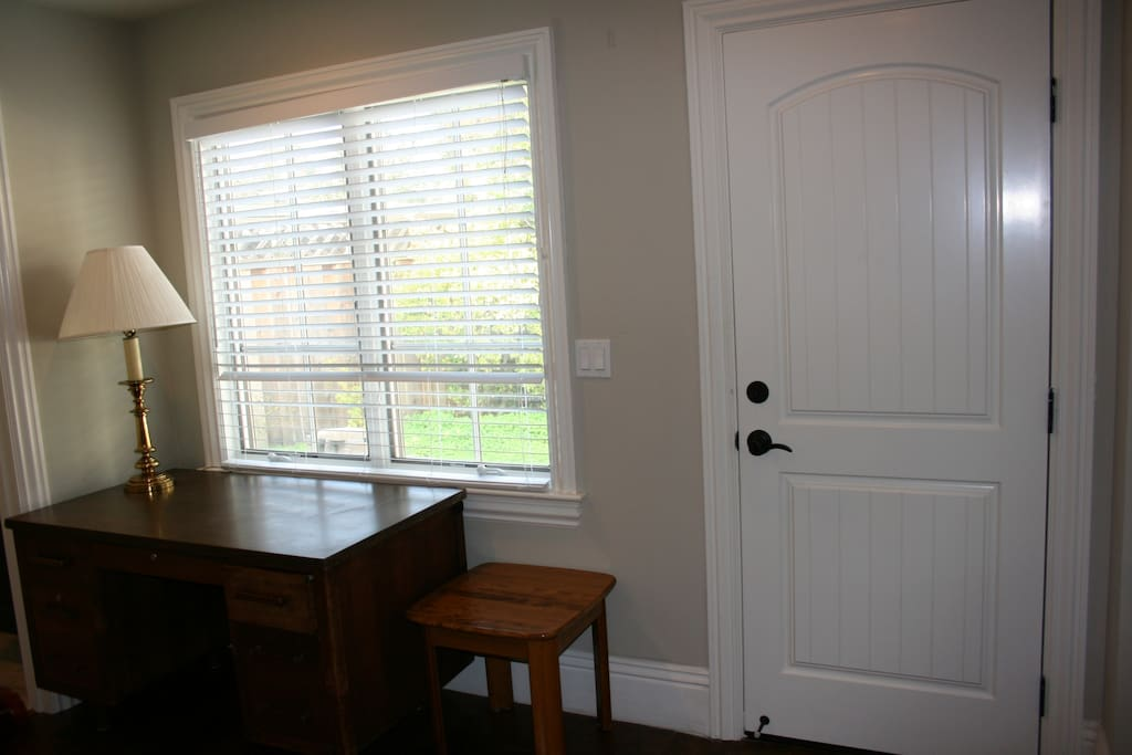 Desk, a big window and entrance door