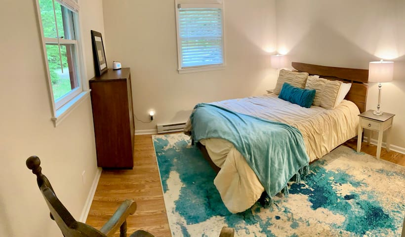 Downstairs bedroom with queen bed, air mattress and rocking chair. Access to main full bathroom just outside the door.