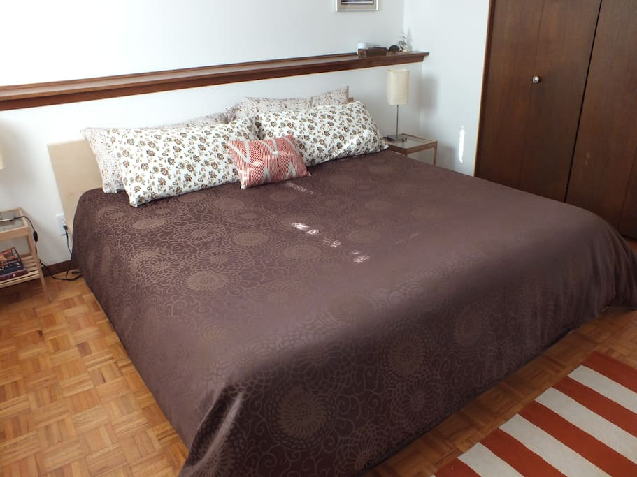 Orange room features a King bed, dresser, night stands, comfy linens, and ample closet.