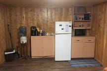 Kitchen area with microwave, coffee pot, refrigerator and 5 gallon water crock.