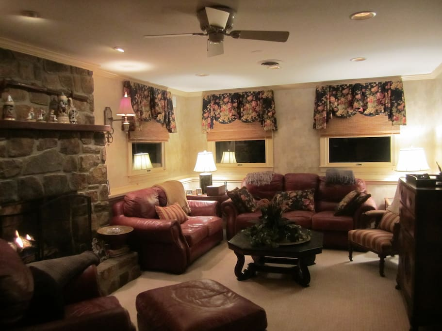 Watch TV from Den with a stone fireplace.