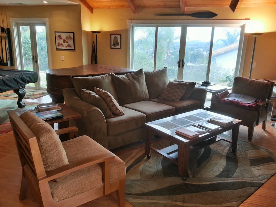 Great Room with comfortable furniture, grand piano, big screen TV, fireplace, french doors, view, and vaulted ceilings.