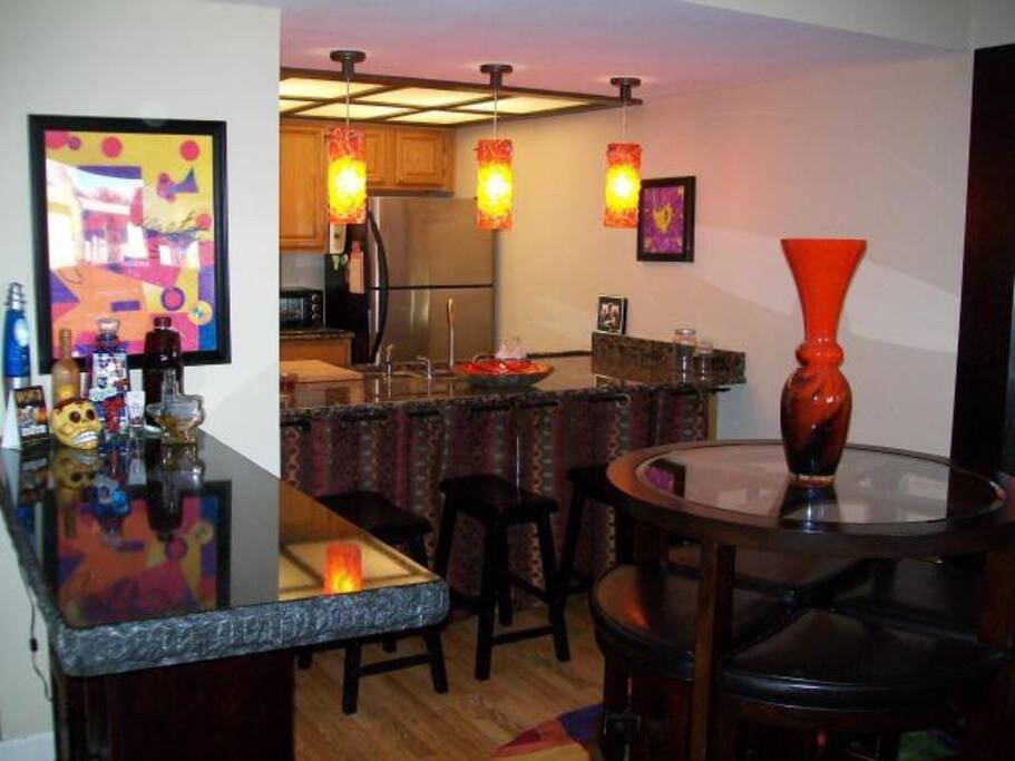 Round table for 4 plus kitchen bar seating 4 more. Additional stand-up bar with granite slab for entertaining.