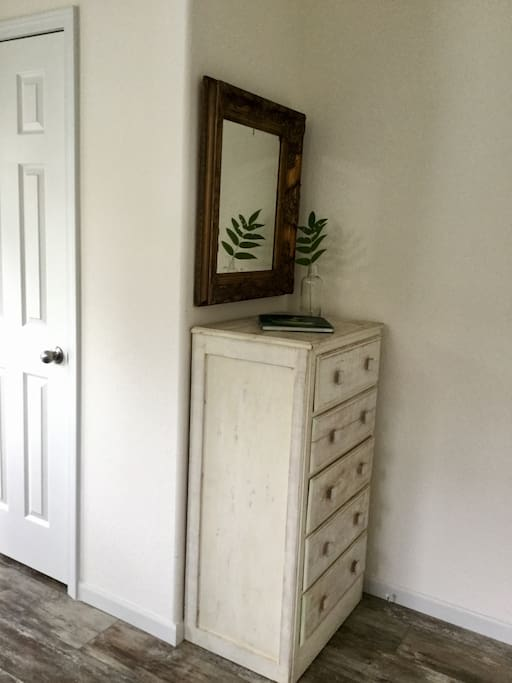 A chest of drawers and closet with wooden hangers for your convenience.