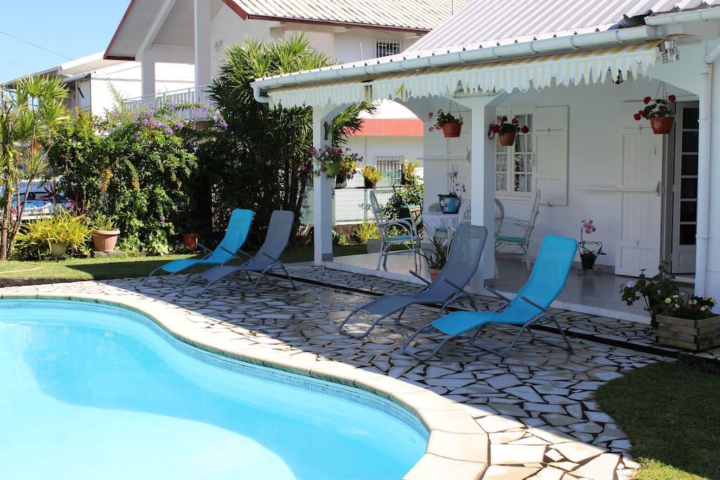 Véranda d'accueil bains de soleil et piscine