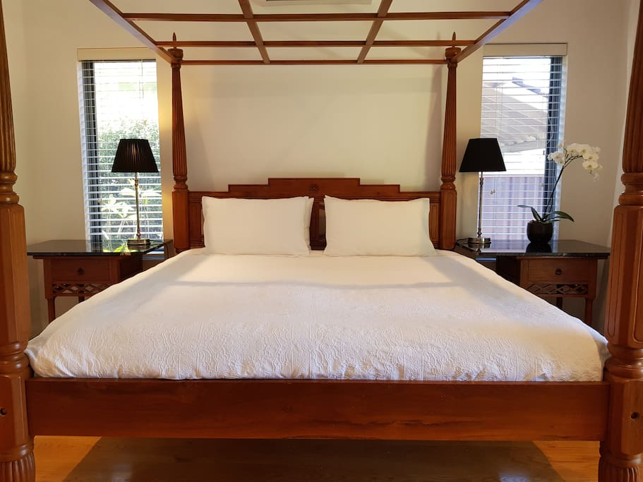 Main bedroom with King size bed and a view of pool,tropical gardens and park.