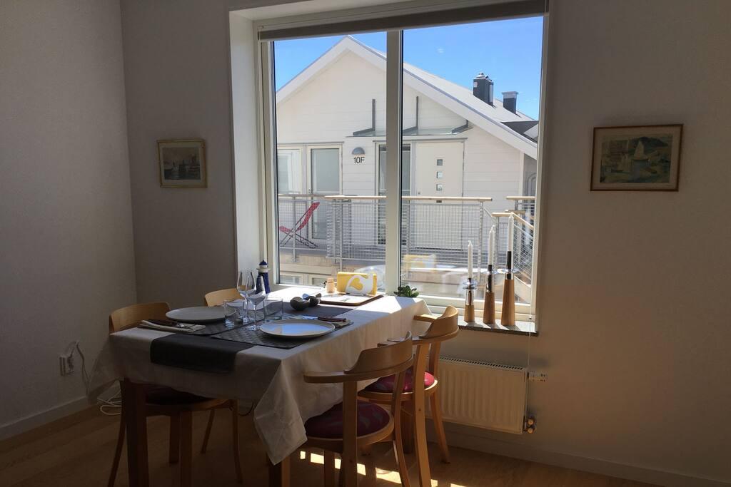 Matbord vid fönster med plisségardin för sol- och insynsskydd