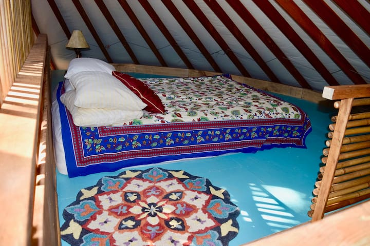 Queen bed in loft.  An adult can stand only at the head of the bed. This is the 2nd of the two sleeping areas