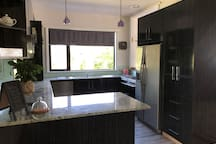 Modern kitchen with granite bench tops. Large windows for views of the garden and the sun going down. Servery through to the lounge room which serves as supervisory point for children or to communicate while you cook.