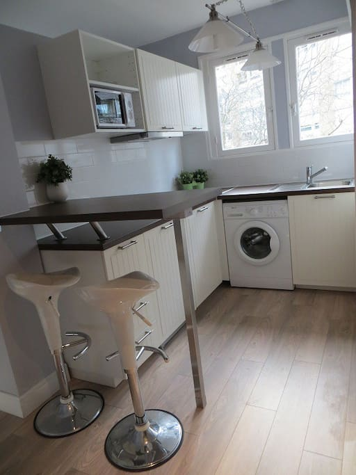 Kitchen with brand new appliances - fridge, washing machine, stove, hood, microwave over and grill.